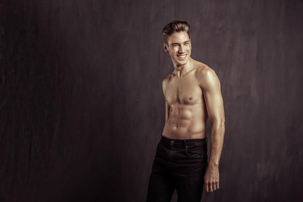 Perfect lichaam. vrolijke aardige man zonder t-shirt terwijl hij zijn perfecte lichaam laat zien