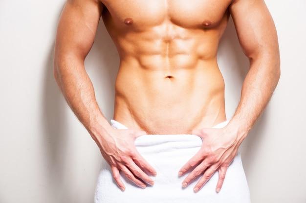 Perfect mannelijk lichaam. close-up, van, jonge, shirtless, man, bedekt, met, handdoek, staand, tegen, witte, background