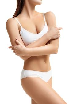 Perfect slank, afgezwakt jong lichaam van het meisje of de fitte vrouw in de studio. het concept van fitness, voeding, sport, plastische chirurgie en esthetische cosmetologie. afbeelding is niet geretoucheerd in lichaamsvorm