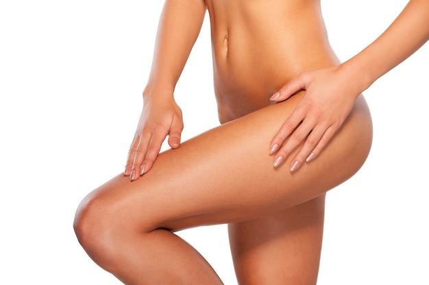 Perfecte billen. bijgesneden afbeelding van mooie jonge shirtless vrouw die haar been aanraakt terwijl ze geïsoleerd op wit staat