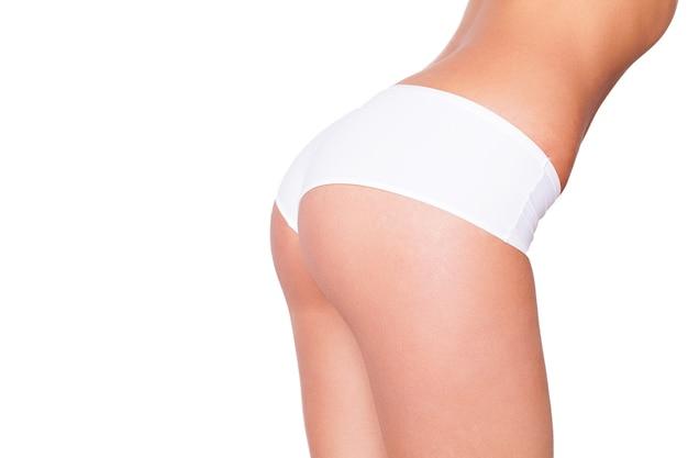 Perfecte billen. mooi lichaam in vorm. zijaanzicht bijgesneden afbeelding van vrouw in witte beha en slipje staande geïsoleerd op wit