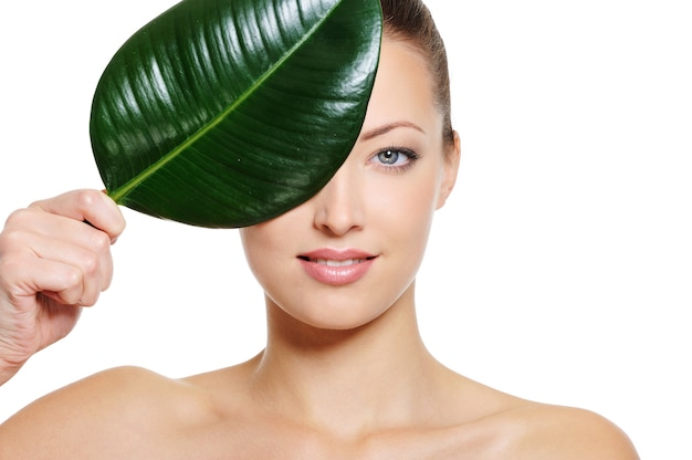 Perfecte blanke vrouw gezicht bedekken met een fris groen blad