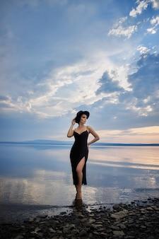Perfecte brunette schoonheidsvrouw in een zwarte hoed en een zwarte jurk poseert in de buurt van een meer tegen een blauwe hemel. lange haarvrouw en mooie schoonheidsmake-up op haar gezicht