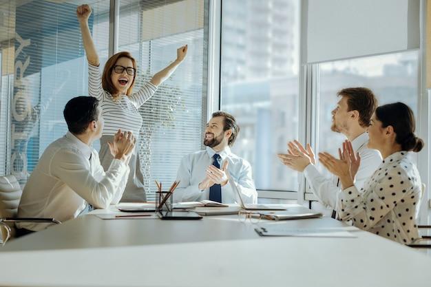 Perfecte dag. schattige jonge vrouw die haar handen in vreugde opheft en haar promotie viert terwijl haar collega's in hun handen klappen en haar feliciteren