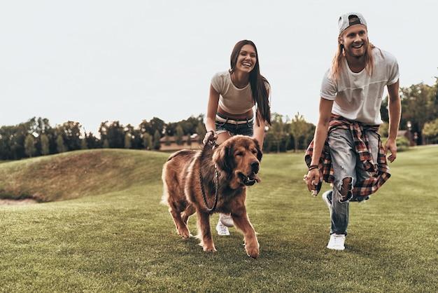 Perfecte harige vriend. volledige lengte van een mooi jong stel dat met hun hond speelt tijdens het rennen in het park