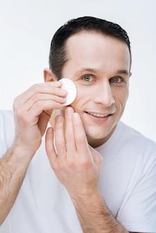 Perfecte huid. positieve aardige vrolijke man die een wattenschijfje vasthoudt en zijn gezicht schoonmaakt terwijl hij er geweldig uit wil zien