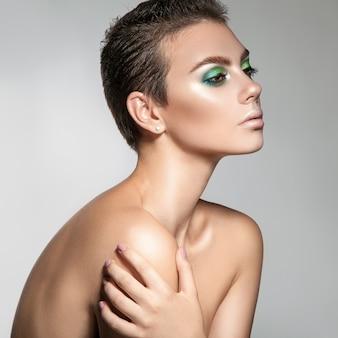 Perfecte jonge vrouw met mooie make-up en kort haar op zoek weg vierkante foto grijze achtergrond