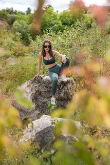 Perfecte kerstvakantie vrouw posign in de buurt van stenen rotsen