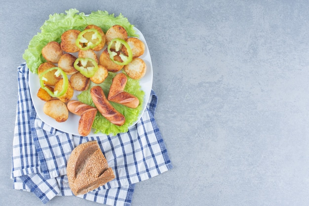Perfecte lunch. worst en aardappel op witte pan met brood.