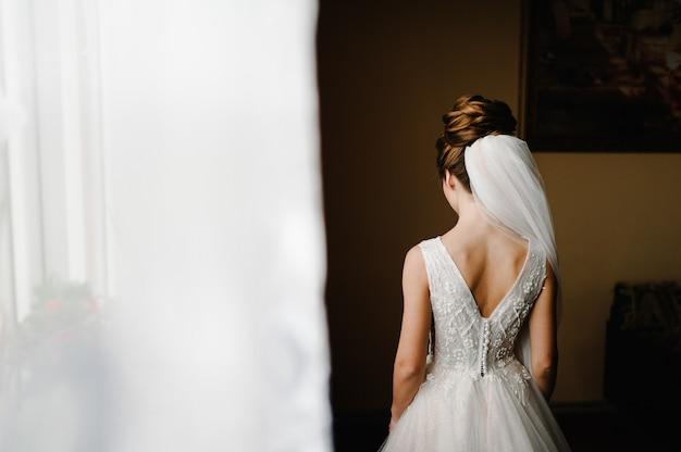 Perfecte mannequinvrouw met kapsel thuis. mooie bruidstijl. bruiloft meisje staan terug in luxe trouwjurk in de buurt van venster.