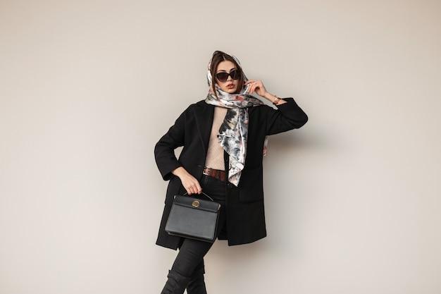 Perfecte mooie jonge professionele vrouw in stijlvolle zonnebril in trendy zwarte jas met leren tas met een vintage sjaal op hoofd poseren in de buurt van een muur buiten. europees meisje. sexy dame mannequin.