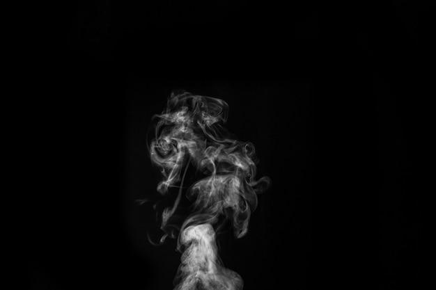 Perfecte mystieke krullende witte stoom of rook geïsoleerd op zwarte achtergrond. abstracte mist of smog als achtergrond, ontwerpelement, lay-out voor collages.