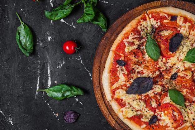 Perfecte pizza margarita met plakjes tomaat, basilicum en kerstomaatjes op een donkere ondergrond