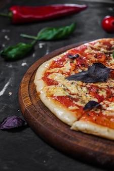 Perfecte pizzamargarita met tomatenplakjes basilicum op een donkere ondergrond