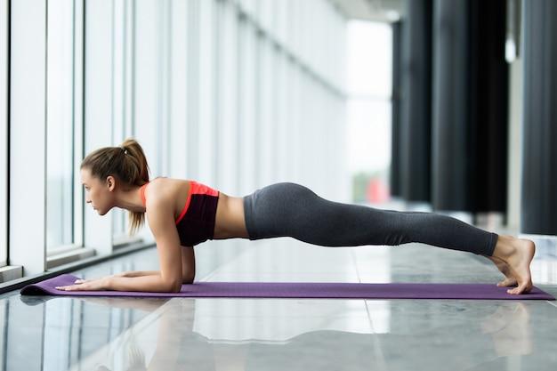 Perfecte plank. zijaanzicht van gemiddelde lengte van jonge mooie vrouw in sportkleding die plank doet terwijl hij voor venster bij gymnastiek