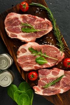 Perfecte rauwe varkenshals met specerijen, rijpe tomaten en verse bladeren op houten snijplank. bovenaanzicht. Premium Foto