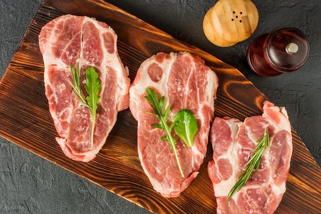 Perfecte rauwe varkenshals met specerijen, rijpe tomaten en verse bladeren op houten snijplank. bovenaanzicht.