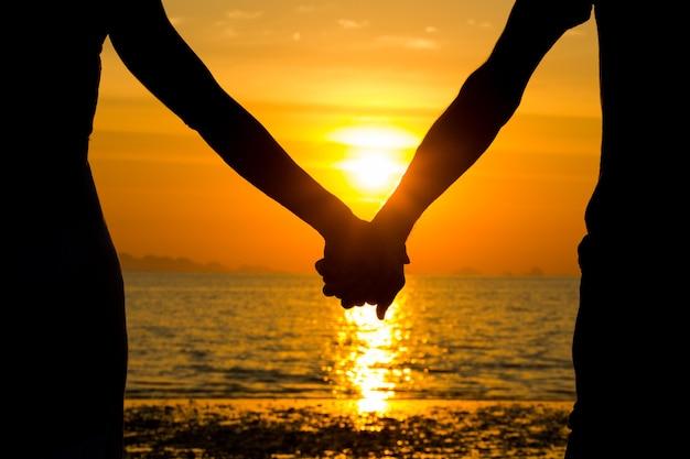 Perfecte scène voor valentijnsdag met het silhouet van een paar hand in hand bij zonsondergang aan zee.