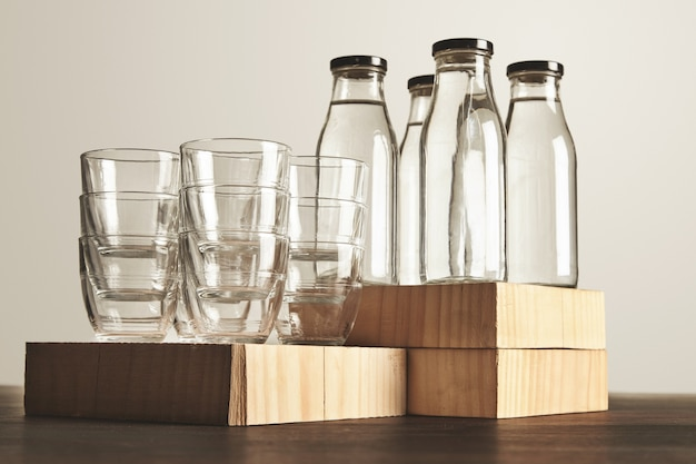 Perfecte set van puur schoon gezond water in transparante glazen flessen en kopjes gepresenteerd op houten