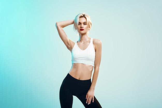 Perfecte sexy jonge vrouw voelen in witte top en zwarte legging die haar blonde haar aanraakt