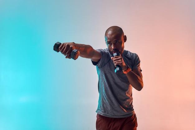 Perfecte spieren sterke jonge afrikaanse man die met halters traint terwijl hij tegen kleurrijk staat
