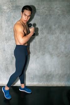 Perfecte sterke bodybuilder atletische aziatische man training arm met halter op achtergrond