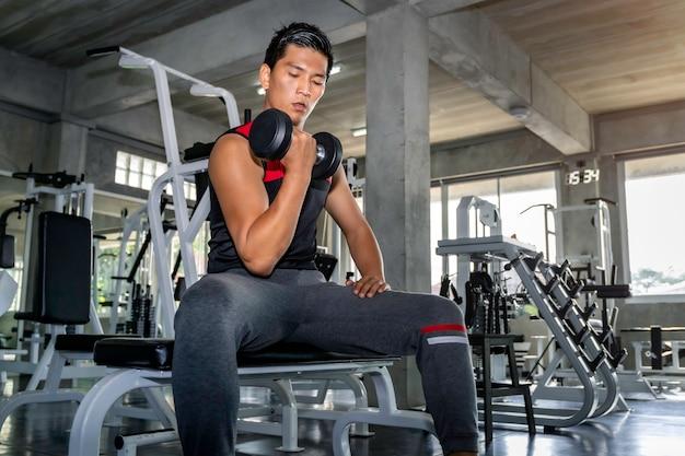 Perfecte sterke bodybuilder atletische aziatische man training arm met halter op sportschool.