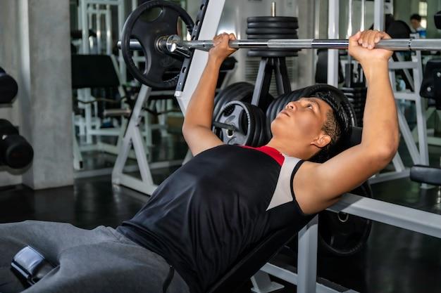 Perfecte sterke bodybuilder atletische aziatische man training borstspieren met barbell op sportschool.