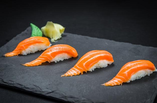 Perfecte sushi, traditionele japanse keuken. heerlijke zalmkiguiri op de versierde plaat, zwarte achtergrond.