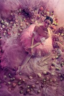 Perfecte uitstraling. bovenaanzicht van mooie jonge vrouw in roze ballet tutu omgeven door bloemen. lentestemming en tederheid in koraallicht. kunst foto. concept van de lente, bloesem en het ontwaken van de natuur.