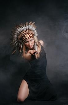 Perfecte vrouw in gewaad van amerikaanse indianen in rook