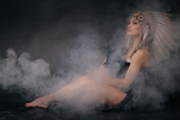 Perfecte vrouw in klederdracht van amerikaanse indianen in rook op een grijze achtergrond. een hoed gemaakt van veren. mysterieuze mystieke manier, sexy lichaam, mooie rug. aantrekkelijke blondine met een mooi gezicht