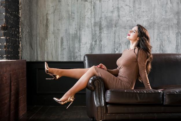 Perfecte vrouwelijke benen die gouden hoge hielen dragen die op bank zitten