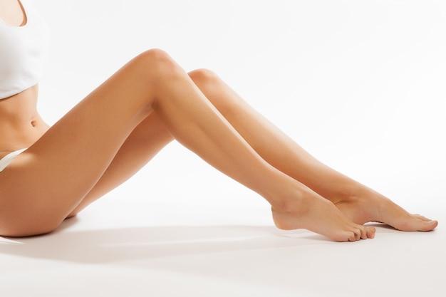 Perfecte vrouwelijke benen, die op witte achtergrond worden geïsoleerd