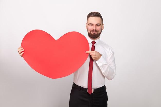 Perfecte zakenman glimlachend, wijzende vinger naar groot rood hart. binnen, studio-opname, geïsoleerd op een grijze achtergrond