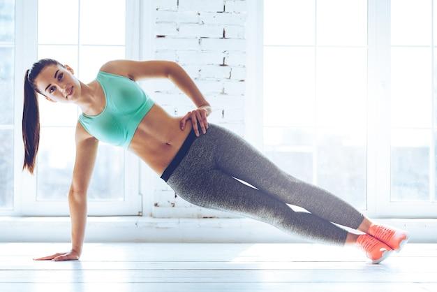 Perfecte zijplank. volledige lengte van jonge, mooie vrouw in sportkleding die zijplank doet en naar de camera kijkt voor het raam in de sportschool
