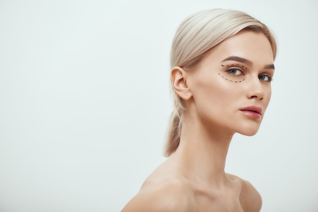 Perfectie mooie en jonge blonde vrouw met zwarte chirurgische lijnen op de oogleden en onder de ogen