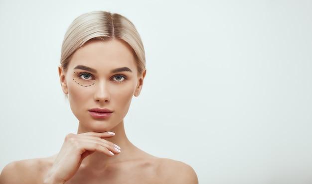 Perforatielijnen mooie en jonge blonde vrouw met zwarte chirurgische lijnen op oogleden en onder