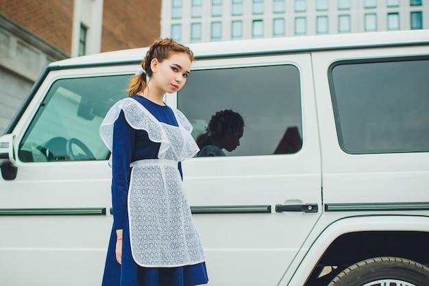 Permanent schoolmeisje met typische navy witte uniforme schort op achtergrond auto Premium Foto