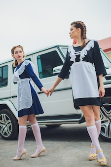 Permanent schoolmeisje met typische navy witte uniforme schort op achtergrond auto