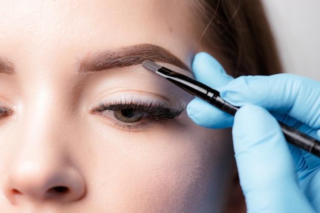 Permanente make-up. permanente tatoeage van wenkbrauwen. cosmetologist die permanente make-up op wenkbrauwen-wenkbrauwtatoegering toepast
