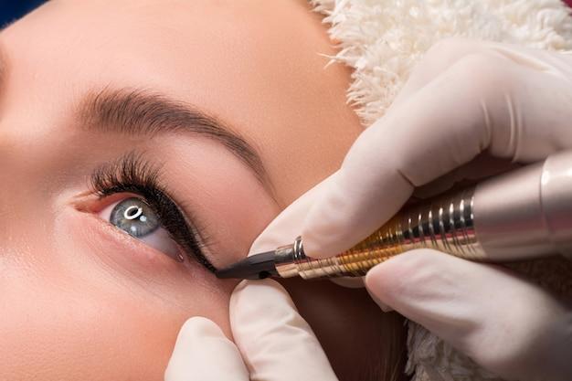 Permanente oogmake-up close-up shot op schoonheidsspecialist tatoeage van ogen toe te passen