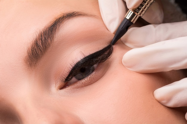 Permanente oogmake-up close-up shot. schoonheidsspecialist tatoeage van ogen toe te passen. make-up eyeliner procedure.