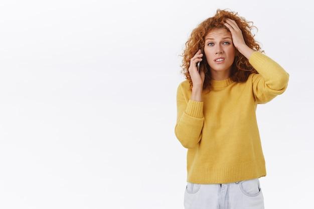 Perplex, besluiteloos roodharige krullende vrouw in gele trui, hoofd aanraken, fronsen, grimassen verbaasd, praten op mobiele telefoon