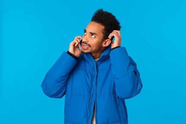 Perplex en besluiteloos jongeman kan zich geen informatie herinneren, weet het antwoord niet, aarzelt wat te zeggen als praten over de telefoon, hoofd krabbend twijfelachtig wegkijkend en smartphone in de buurt van oor, blauwe achtergrond