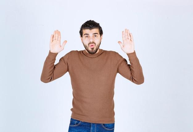 Perplex jongeman man in bruine trui poseren met stijgende handen omhoog. hoge kwaliteit foto