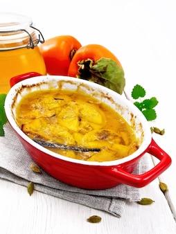 Persimmon gebakken met honing, kardemom en vanille in een braadpan op een handdoek, munt en sinaasappelfruit op houten plankachtergrond