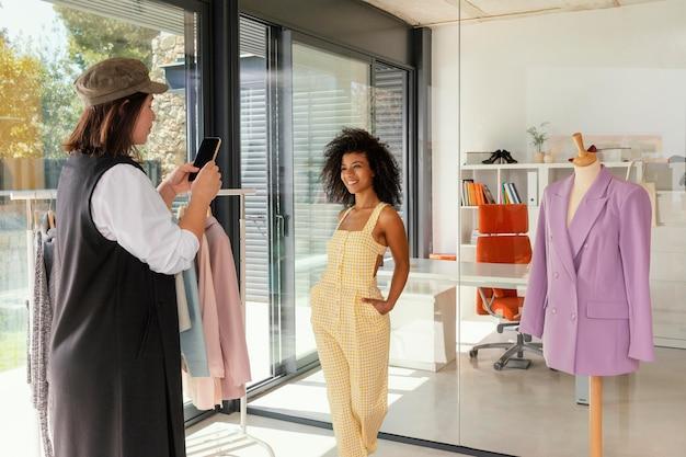 Personal shopper op kantoor met klant die foto's maakt