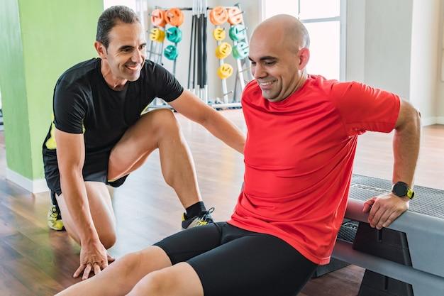 Personal trainer die een man helpt om pull-ups te doen op de vloer in een sportschool