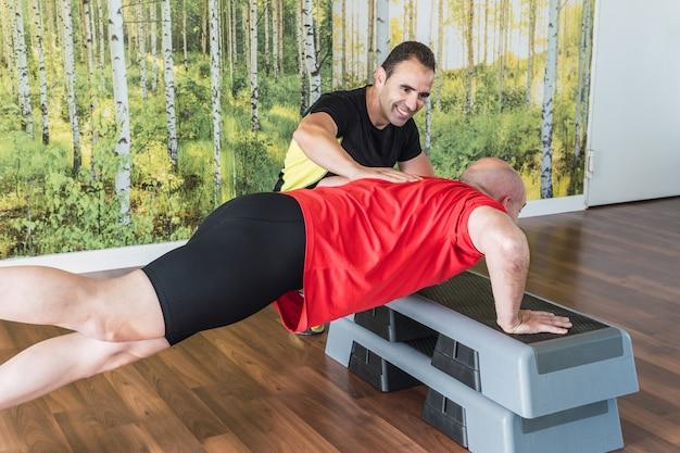 Personal trainer die een man helpt push-ups te doen op de vloer in een sportschool